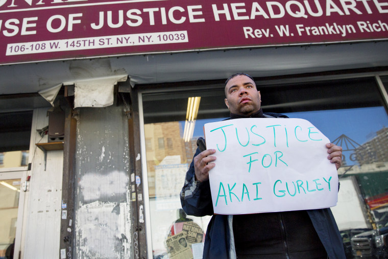 A man stands in front of the National Action Network on Nov. 22, 2014 in N.Y. after Rev. Al Sharpton spoke about the shooting of Akai Gurley. (Photo by Craig Ruttle/AP)