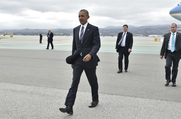 President Obama walks across the tarmac to greet well-wishers upon arrival at San Francisco International Airport, April 8, 2016. (Photo by Mandel Ngan/AFP/Getty)