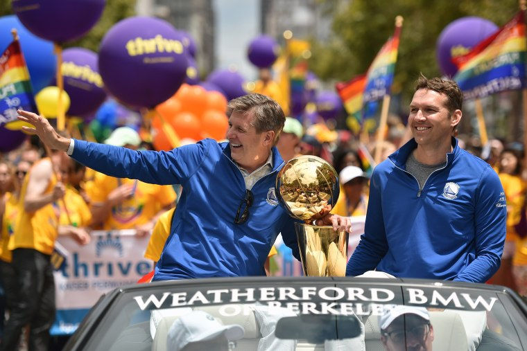 Golden State Warriors President and COO Rick Welts waves to the crowd while holding the NBA championship trophy during the annual Gay Pride Parade in San Francisco, Calif., June 28, 201. (Photo by Josh Edelson/AFP/Getty)