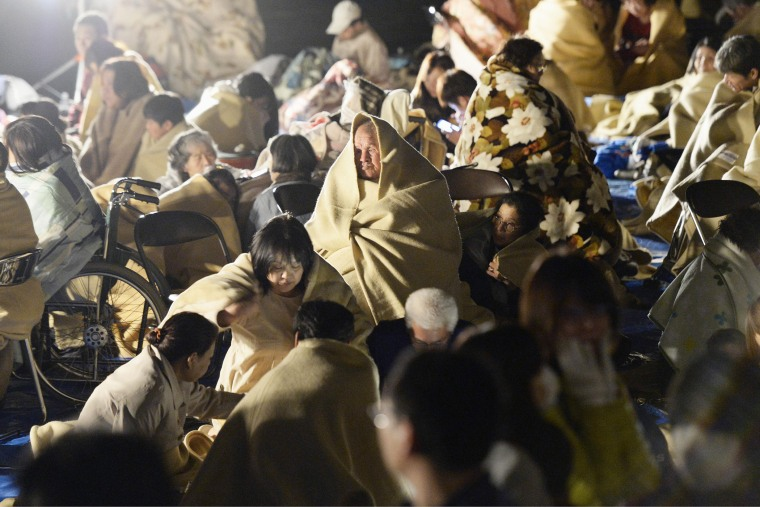 Residents wrap themselves in blankets as they take shelter outside the town hall of Mashiki, near Kumamoto city, southern Japan, after the earthquake early April 15, 2016. (Photo by Ryosuke Uematsu/Kyodo News/AP)
