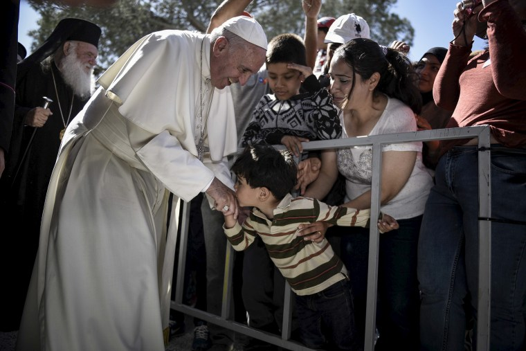 A boy shakes the hand of Pope Francis as he greets migrants and refugees at Moria refugee camp near the port of Mytilene, on the Greek island of Lesbos, April 16, 2016. (Photo by Andrea Bonetti/Greek PM Press Office/Handout/Reuters)