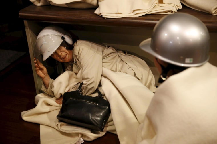 A woman takes shelter after another earthquake hit the area at a hotel in Kumamoto, southern Japan, in this photo taken by Kyodo April 16, 2016. (Photo by Kyodo/Reuters)