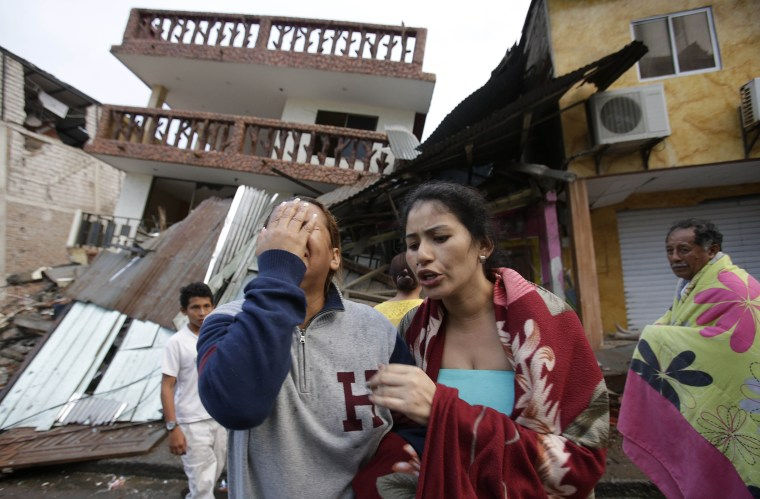 A woman cries as she stands next to house destroyed by the earthquake in the Pacific coastal town of Pedernales, Ecuador, April 17, 2016. (Photo by Dolores Ochoa/AP)