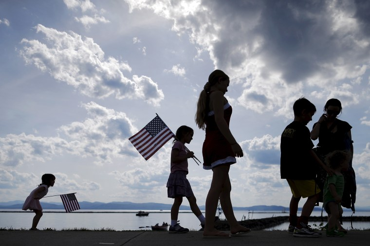 A Vermont family waits for U.S. Senator Bernie Sanders to kick off his presidential campaign on the shore of Lake Champlain in Burlington, which is lined by New York mountains on the horizon, May 26, 2015. (Photo by Brian Snyder/Reuters)