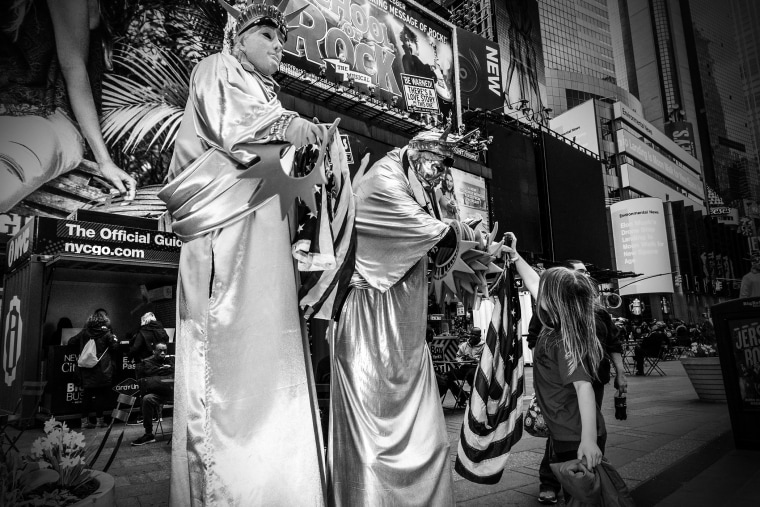 A young girl takes a souvenir from a Statue of Liberty character in Times Square, New York City, April 17, 2016. (Photo by Mark Peterson/Redux for MSNBC)