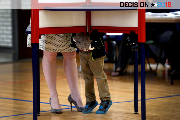 A woman fills out her ballot in a voting booth in the New York, in the U.S. presidential primary election, as her young son looks on, Grafflin School in Chappaqua, N.Y., April 19, 2016. (Photo by Mike Segar/Reuters)