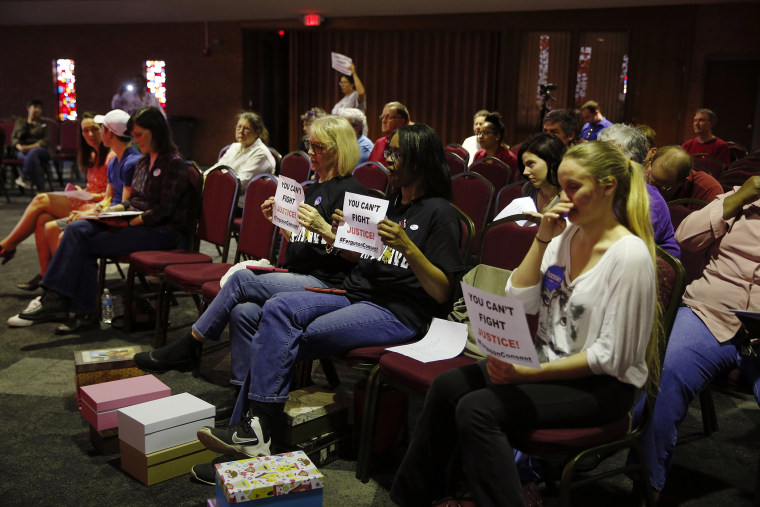 In this March 15, 2016 file photo, people watch and hold signs as members of the Ferguson City Council meet in Ferguson, Mo. (Photo by Jeff Roberson/AP)