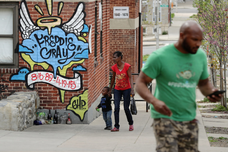 Neighbors walk past the spot where Baltimore police arrested Freddie Gray at the Gilmor Homes in the Sandtown neighborhood one year after Gray died April 19, 2016 in Baltimore, Md. (Photo by Chip Somodevilla/Getty)