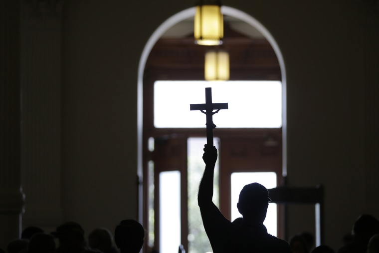 A man carries a cross. (Photo by Eric Gay/AP)