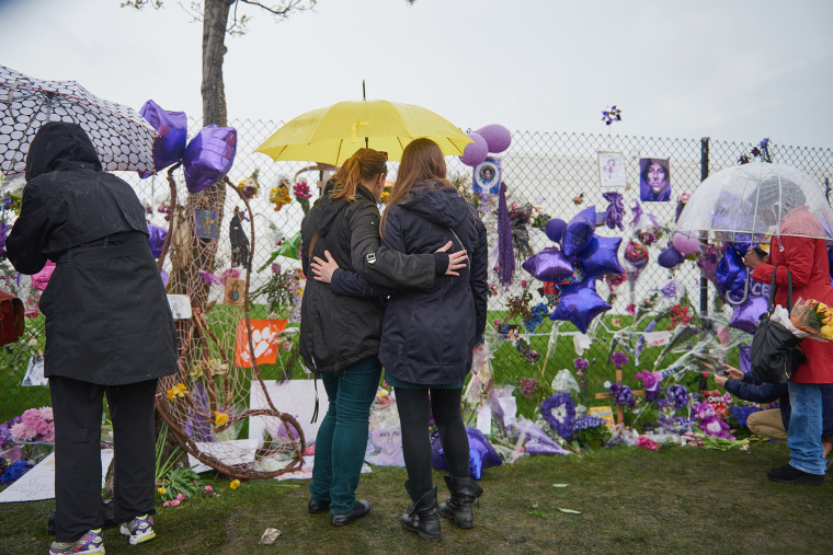 Two Prince fans embrace in front of the memorial outside Paisley Park on April 24, 2016 in Chanhassen, Minn. (Photo by Jules Ameel/Getty)