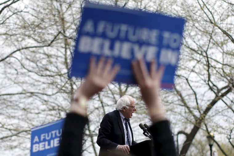 U.S. Democratic presidential candidate Bernie Sanders is seen between the arms a supporter waving a sign as he speaks at a campaign rally in Hartford, Conn. on April 25, 2016. (Photo by Mike Segar/Reuters)