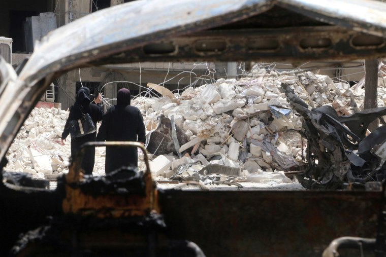 Women walk past damage near al-Quds hospital after it was hit by airstrikes, in a rebel-held area of Syria's Aleppo, April 28, 2016. (Photo by Abdalrhamn Ismail/Reuters)