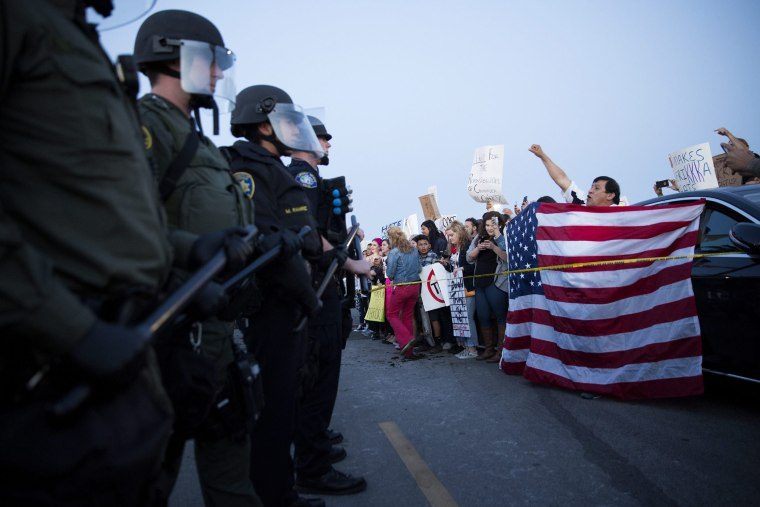 Protesters opposed to US Republican presidential candidate Donald Trump are separated from supporters by a line of riot police officers outside Trump's campaign rally in Costa Mesa, Calif., on April 28. 2016. (Photo by Eugene Garcia/EPA)