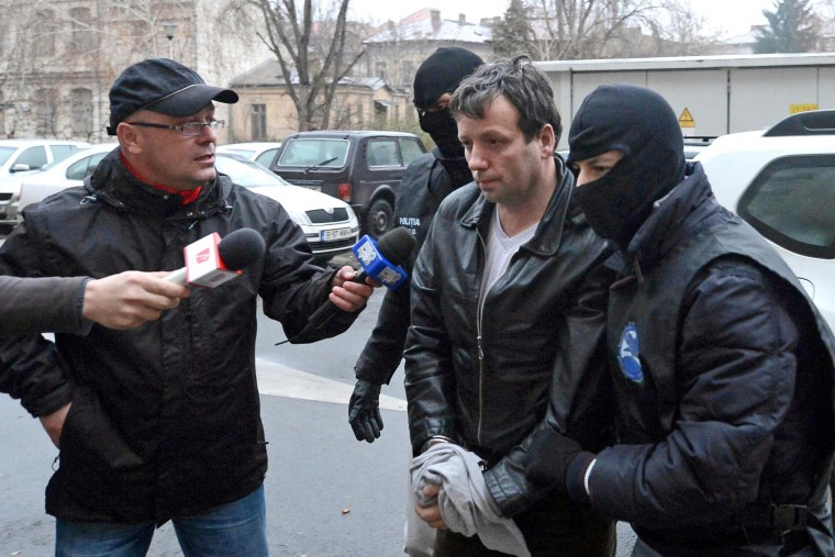 Marcel Lazar Lehel, 40, is escorted by masked policemen in Bucharest, after being arrested in Arad, 550 km (337 miles) west of Bucharest, Jan.22, 2014. (Photo by Silviu Matei/Mediafax/Reuters)