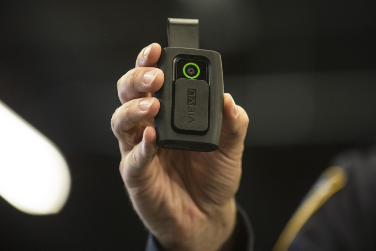 NYPD Sergeant Joseph Freer demonstrates how to use and operate a body camera during a media press conference on Dec. 3, 2014 in New York City. (Photo by Andrew Burton/Getty)