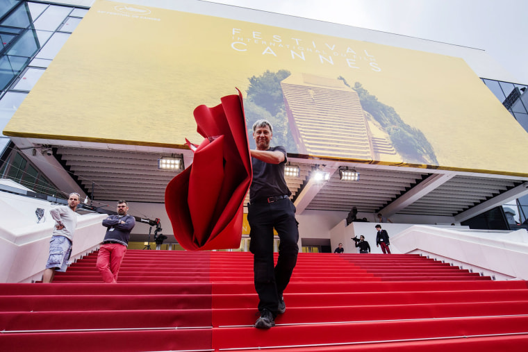 A worker installs the red carpet in front of the Festival Palace ahead of the 69th Cannes Film Festival, in Cannes, France, May 10, 2016. (Photo by Julien Warnand/EPA)