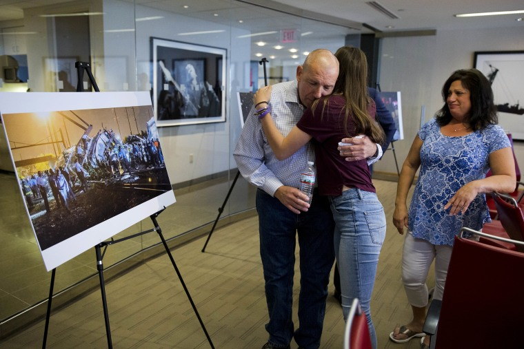 Amtrak crash survivor Robert Hewett embraces his daughter Emily as his wife Judy, right, looks on after a news conference, May 12, 2016, in Philadelphia. (Photo by Matt Rourke/AP)