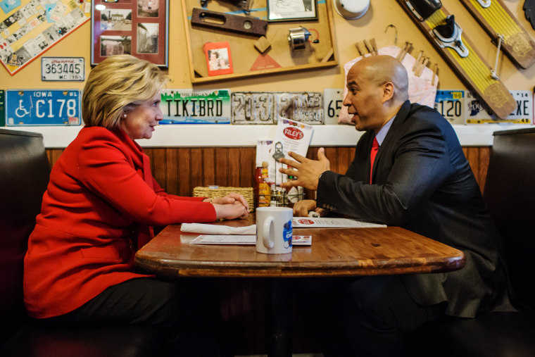 Democratic presidential candidate Hillary Clinton talks with Sen. Cory Booker (D-NJ) at Riley's Cafe on Jan. 24, 2016 in Cedar Rapids, Iowa. (Photo by Brendan Hoffman/Getty)