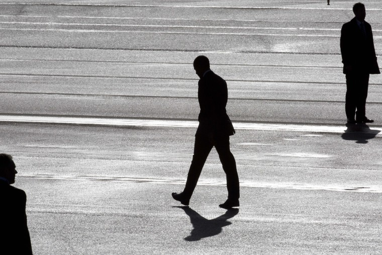 President Barack Obama, center, and two secret service agents are silhouetted as he walks towards Marine One helicopter upon arrival at Schiphol Amsterdam Airport, Netherlands March 24, 2014. (Photo by Peter Dejong/Pool/AP)