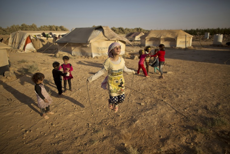 Syrian refugee girl, Zubaida Faisal, 10, skips a rope while she and other children play near their tents at an informal tented settlement near the Syrian border on the outskirts of Mafraq, Jordan, July 19, 2015. (Photo by Muhammed Muheisen/AP)