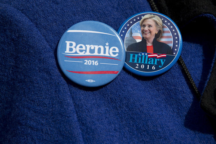 A voter wears buttons for Democratic presidential candidates Sen. Bernie Sanders, I-Vt., and Hillary Clinton buttons, March 31, 2016, in New York. (Photo by Mary Altaffer/AP)