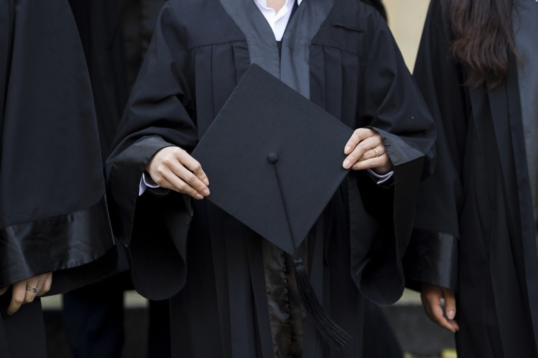 A graduate holds her cap before celebrating her graduation. (Photo by Jens Schlueter/Getty)