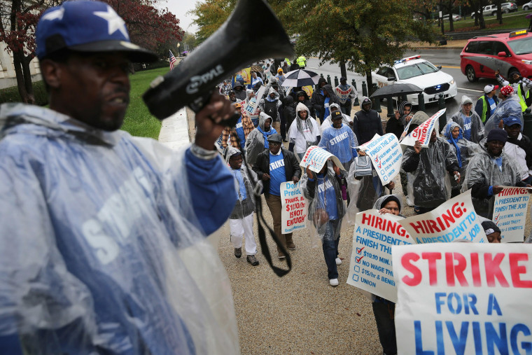 Demonstrators march along Constitution Avenue during a protest to call for higher wages for government contract workers on Capitol Hill Nov. 10, 2015 in Washington, DC. (Photo by Chip Somodevilla/Getty)