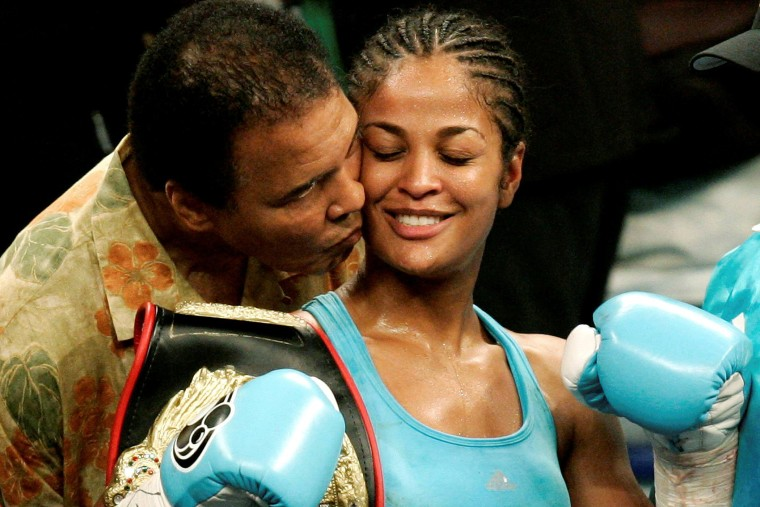 WBC and WIBA super middleweight champion Laila Ali is kissed by her father, boxing great Muhammad Ali, at the MCI Center in Washington on June 11, 2005. (Photo by Jason Reed/Reuters)