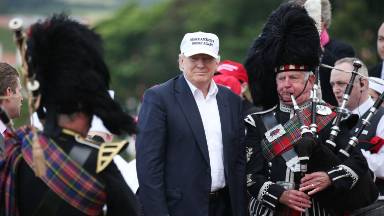 The presumptive Republican presidential nominee Donald Trump poses with a bagpiper as he arrives at his revamped Trump Turnberry golf course in Turnberry Scotland, June 24, 2016. (Photo by Andrew Milligan/PA/AP)
