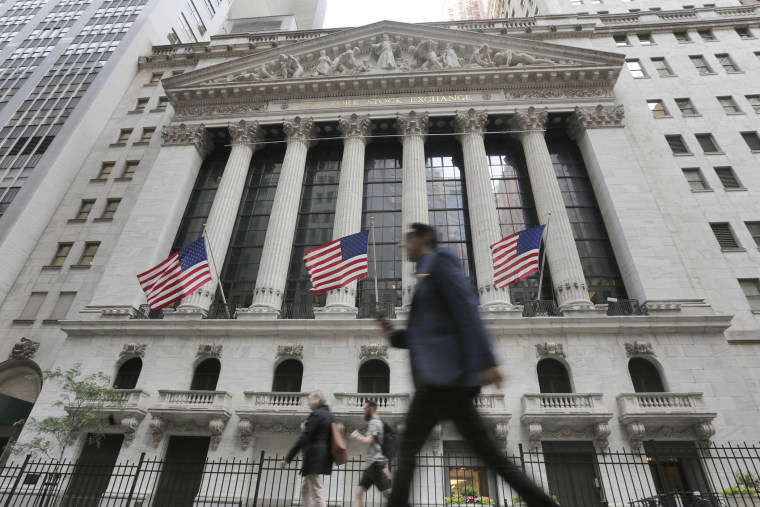 People pass the New York Stock Exchange, June 24, 2016 in New York, N.Y. (Photo by Richard Drew/AP)