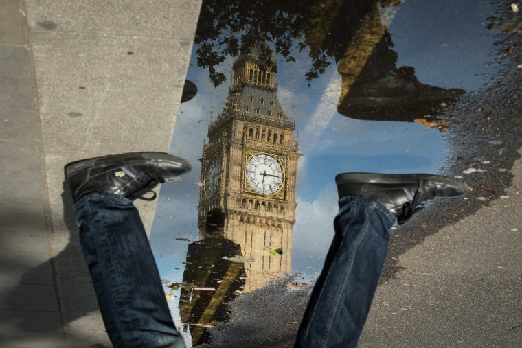 The Queen Elizabeth Tower (Big Ben) is reflected in a puddle as a man walks by on June 27, 2016 in London, England. (Photo by Leon Neal/AFP/Getty)