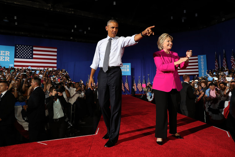 Democratic presidential candidate former Secretary of State Hillary Clinton (R) and U.S. president Barack Obama greet supporters during a campaign rally on July 5, 2016 in Charlotte, N.C. (Photo by Justin Sullivan/Getty)