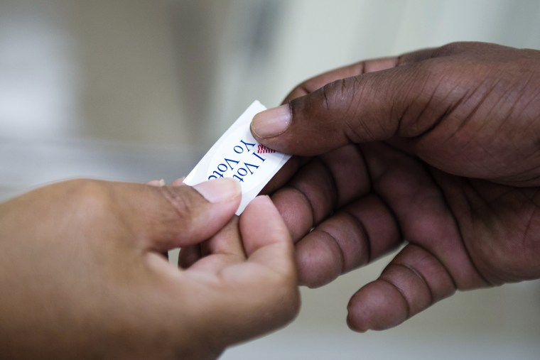 An 'I voted' sticker is handed out to a voter during the Maryland presidential primary election at Skyline Elementary School in Suitland, Md., April 26, 2016. (Photo by Shawn Thew/EPA)