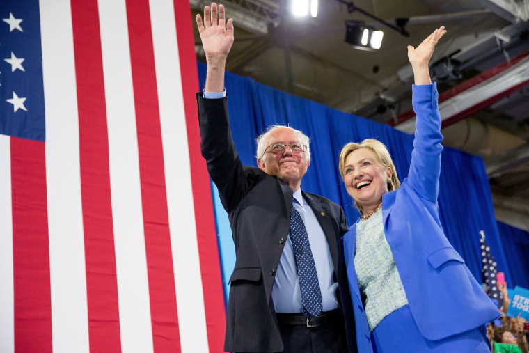 Democratic presidential candidate Hillary Clinton and Sen. Bernie Sanders, I-Vt., wave to supporters as Sanders endorsed Clinton during a rally in Portsmouth, N.H., July 12, 2016. (Photo by Andrew Harnik/AP)