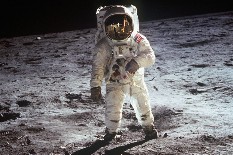 """American astronaut Edwin \""""Buzz\"""" Aldrin walking on the moon on July 20, 1969 during Apollo 11 mission. Neil Armstrong's reflection in the visor of the helmet. (Photo by Apic/Getty Images)"""