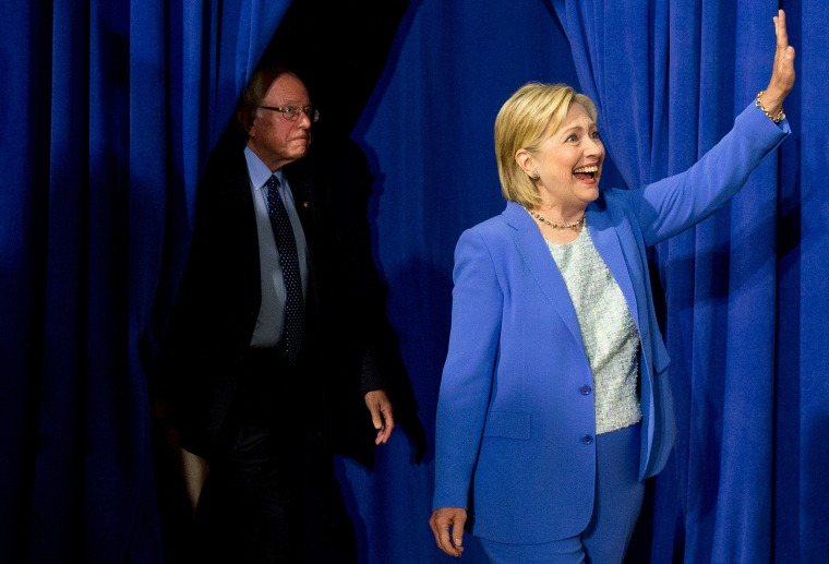 Democratic presidential candidate Hillary Clinton, followed by Sen. Bernie Sanders, I-Vt., waves as they arrive for a rally in Portsmouth, N.H., July 12, 2016, where Sanders endorsed Clinton for president. (Photo by Andrew Harnik/AP)