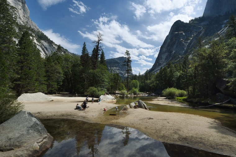 People picnic on the exposed sandy bottom of Mirror Lake that is normally underwater and used by visitors to photograph reflections of the Half Dome rock monolith, June 4, 2015, at Yosemite National Park in Calif. (Photo by Mark Ralston/AFP/Getty)