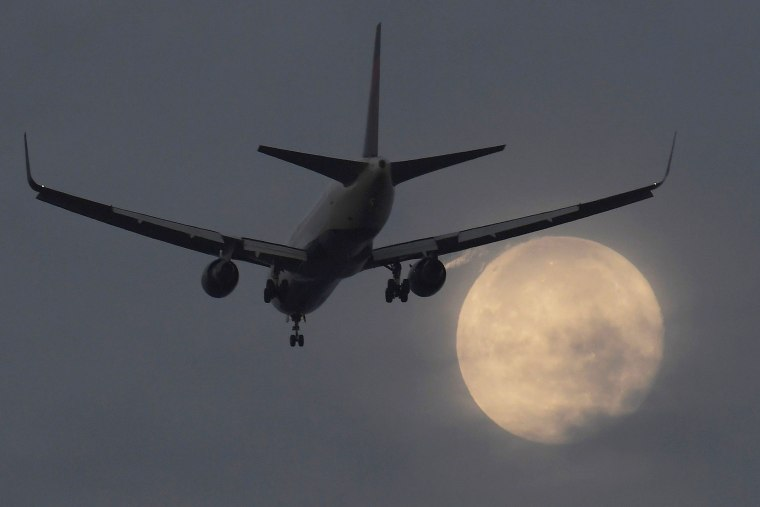 "A passenger aircraft makes its landing approach to Heathrow airport in front of a ""super moon"" at dawn in west London, Britain on Oct. 17, 2016. (Photo by Toby Melville/Reuters)"