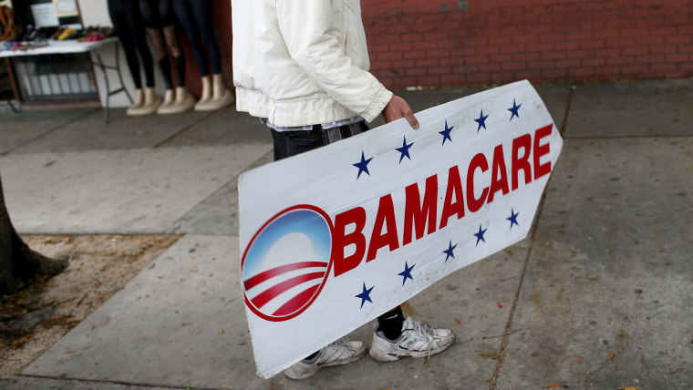 A man holds a sign directing people to an insurance company where they can sign up for the Affordable Care Act, also known as Obamacare in Miami, Fla in 2015. (Photo by Joe Raedle/Getty)