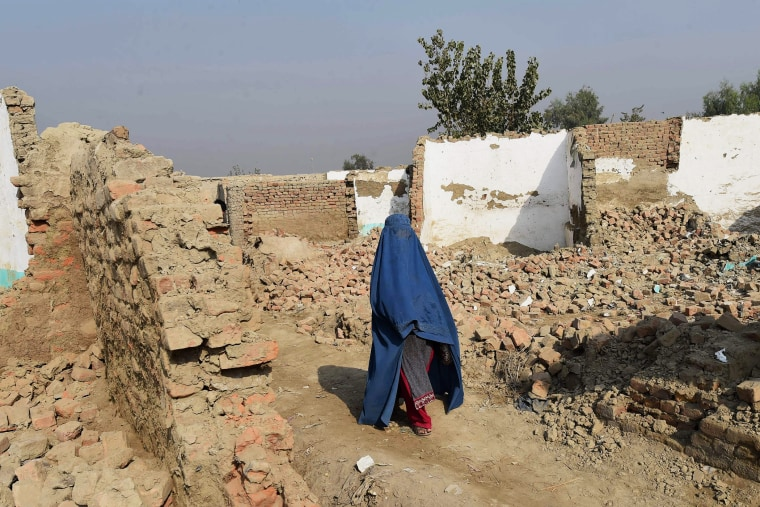 A Burqa-wearing Afghan refugee crosses in front of demolished houses in the Khazana refugees camp outskirts of Peshawar on Oct. 24, 2016. (Photo by A Majeed/AFP/Getty)