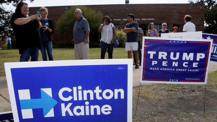 Early voters stand by campaign signs as they wait in line at a voting location in Dallas, Oct. 27, 2016. (Photo by Tony Gutierrez/AP)