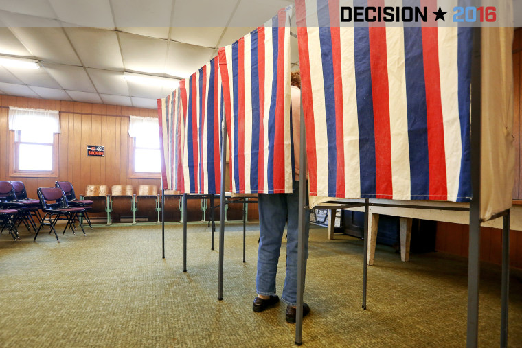 A voter casts a ballot behind a curtain at Smelser Town Hall, Nov. 8, 2016, in Georgetown, Wis. (Photo by Nicki Kohl/Telegraph Herald/AP)