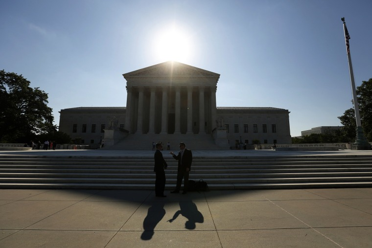 Two men talk as the sun rises over the Supreme Court in Washington, D.C. (Photo by Kevin Lamarque/Reuters)
