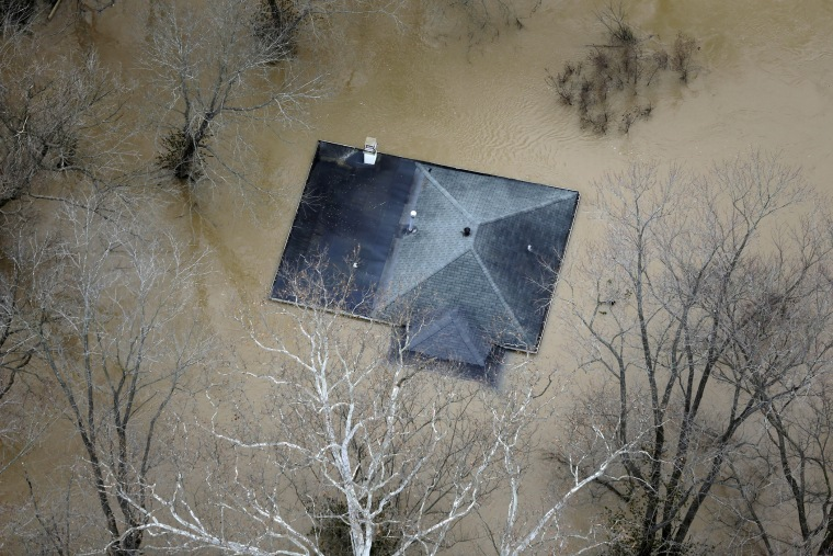 In this aerial photo, floodwater reaches the rooftop of a house, Dec. 31, 2015, in Valley Park, Mo. (Photo by Jeff Roberson/AP)