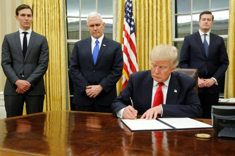 Image: Trump, flanked by Kushner, Pence and Porter, welcomes reporters into the Oval Office for him to sign his first executive orders at the White House in Washington
