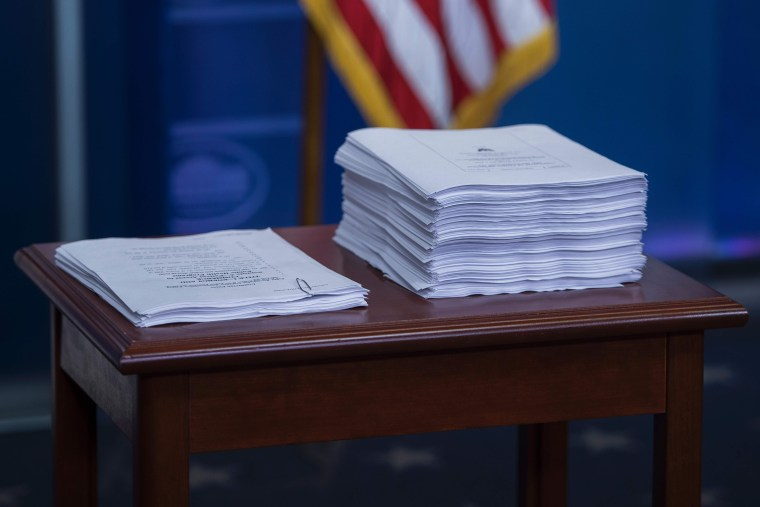 A print-out of the Affordable Care Act (ACA) (R) sits next to a copy of the plan introduced to repeal and replace the ACA during the daily briefing at the White House in Washington, DC on March 7, 2017.