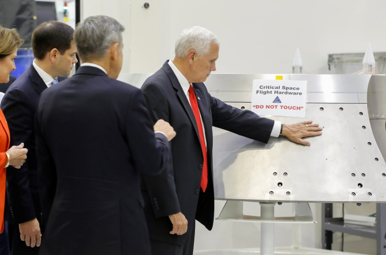 "Image: U.S. Vice President Mike Pence touches a piece of hardware with a warning label ""Do Not Touch"" at Kennedy Space Center in Florida"