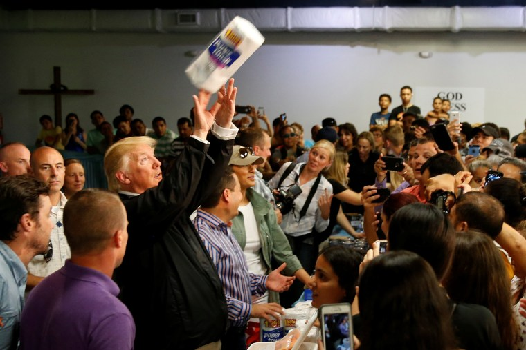 Image: U.S. President Trump tosses rolls of paper towels to people at a hurricane relief distribution center at Calvary Chapel in San Juan