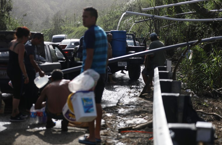 People fill containers with water funneled with pipes from a mountain stream in Utuado, Puerto Rico.