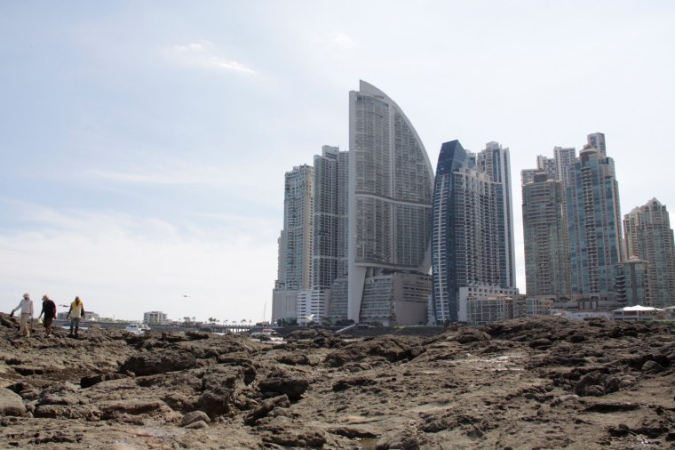 Image: People stand on rocks on the shore during low tide as the Trump Ocean Club International Hotel and Tower Panama is seen next to apartment buildings in Panama City